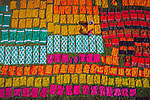 Workers lay out brightly coloured cloth to dry in the sun by