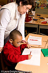 Parochial School Bronx New York  Kindergarten female teacher working with child on writing assignment vertical