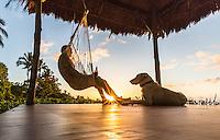 A man and his dog enjoy the sunset in their gazebo, Waialua, O'ahu.