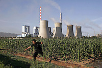 A man leaps across a irrigation ditch close to the Shengtou No. 2 Power Plant near Shuozhou, Shanxi Province, China. Power plants such as this one in China's rural provinces in the north supply over two thirds of Beijing's electricity and suffers environmental pollution and even local brown-outs to guarantee the capital's power demand..