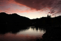 Mountains draw a jagged dividing line as sunset paints the clouds overhead and the water below at Donner Lake.