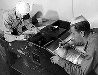 Students of Class III Aerial Photography preparing negatives for printing. W. E. Anderson (left) and J. Filipowicz number their aerial negatives.