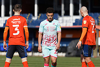 Joel Latibeaudiere of Swansea City (C) between Dan Potts (L) and Kal Naismith of Luton Town (R) during the Sky Bet Championship match between Luton Town and Swansea City at Kenilworth Road, Luton, England, UK. Saturday 13 March 2021