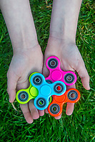 A young boy holds a green, blue, orange and pink fidget spinners