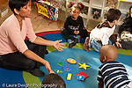 Education preschool 3-4 year olds circle time female teacher with collection of geometric shapes on floor in front of her horizontal some children distracted or looking away attention span