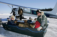 """Monday March 12, 2007   ----   Iditarod air force pilot Danny Davidson and """"Teacher on the Trail"""" Kim Slade sit with 5 dropped dogs in a sled as it pulls up to pilot Greg Nieson's plane at the airport at Kaltag to be flown to Unalakleet."""