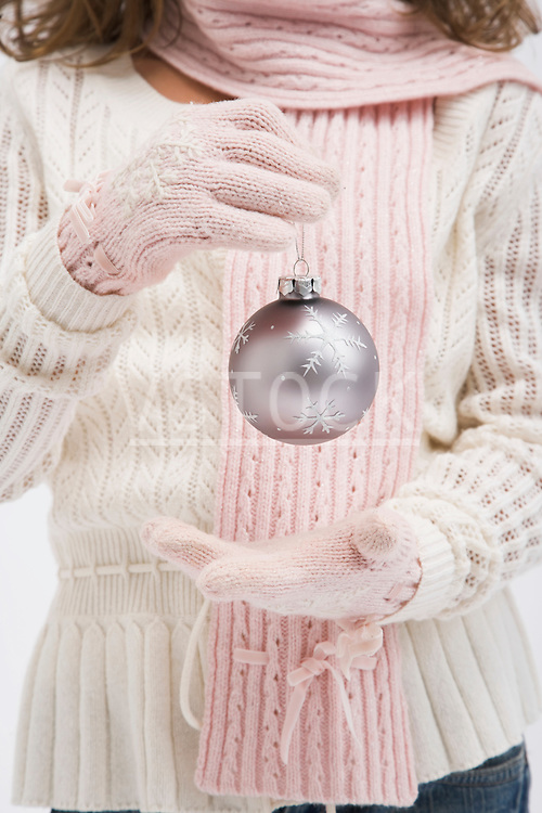 Girl wearing gloves holding christmas bauble, mid section