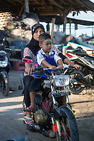 Jimbaran, Bali, Indonesia.  Mother and Son Riding Motorbike, No Helmets.