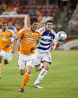 Houston Dynamo defender Bobby Boswell (32) and FC Dallas forward Kenny Cooper (33) chase down the ball.  Houston Dynamo defeated FC Dallas 1-0 at Robertson Stadium in Houston, TX on May 9, 2009
