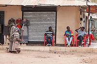 Tanzania, Mto wa Mbu Street Scene, Three Younbg Men Relaxing.