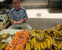 "A fruit seller end up eating is own stock because of customer shortage after the economic blockade imposed on them after the victory of Hamas in the legislative elections last year May.20.2007""photo by Fady Adwan"""
