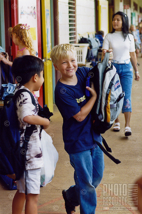Elementary school hallway with children putting on backpacks after class