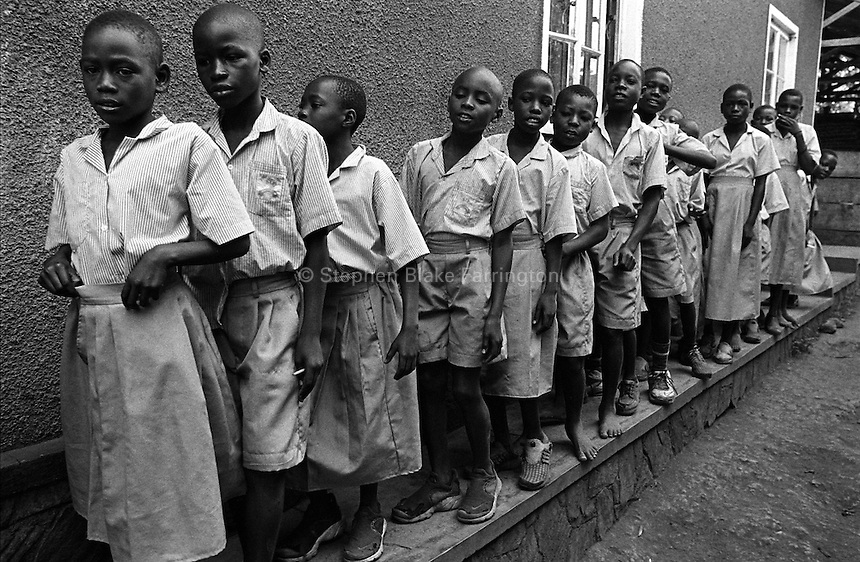 Primary three lined up in the yard at Rehaboth Integrated School. Most of the 130 plus children that attend this school are orphans due to HIV/AIDS. Uganda has an estimated 1.5 million people infected with HIV/AIDS and contains over 1 million orphans. Bugembe, Jinja District, Uganda, Africa. June 2004 © Stephen Blake Farrington