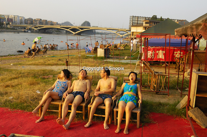 Chinese tourists relaxing on chairs after swimming in the Li River at beach opposite the city centre in Guilin, China. The Li River meanders its way for about 170kms, passing through the Guilin, Yangshuo to the outlet of the Gongchen River in the Pingle Country, and is known for clear and spectacular reflections of the hills surrounding it..03 Oct 2006