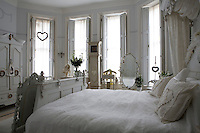 The bedroom has four large windows dressed with sheer curtains and wooden shutters