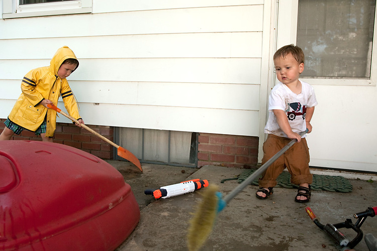 """Brothers, age four, left, and age two, right, switch to feverishly """"cleaning"""" our back patio after cooling off with hose and squirt gun on a hot day."""