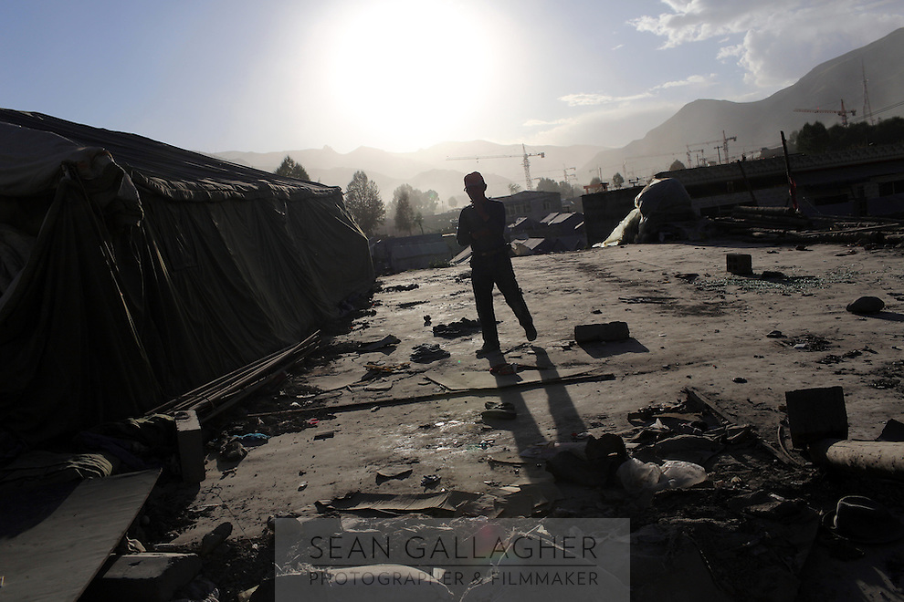 A man walks through a construction site in the town of Yushu on the Tibetan Plateau, in western China.