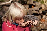 Kind mit Igel in der Hand, Europäischer Igel im Garten, Erinaceus europaeus, Western hedgehog, Westigel, Braunbrustigel, Hérisson d`Europe de l`Ouest