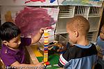 Preschool Headstart 3-5 year olds two boys playing with Lego plastic bricks construction horizontal