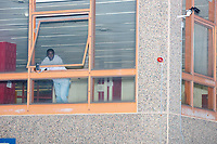 A man watches from the window of the Madison Park Technical Vocational School as a group of at least 1000 people marched in Boston, Massachusetts, on Fri., Sept. 25, 2020, to demand justice for the police killing of Breonna Taylor after this week's announcement that the Louisville, Kentucky, police officers would not be charged. The group marched from Nubian Square in Roxbury to the Boston Police Department Headquarters and then to downtown Boston. The killing of Breonna Taylor, along with the killing of other people of color by police in 2020 and previously, has led to widespread protest and demonstration throughout the country. This week's decision not to charge the officers in her killing has led to a recharged protest movement in Boston and elsewhere.