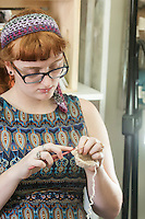 STAFF PHOTO ANTHONY REYES • @NWATONYR<br /> ALL NAMES CQUED<br /> B'ney Landis, of Gentry, crochets a slipper Thursday, Sept. 18, 2014 during a crocheting and knitting class at Mockingbird Moon in Rogers.