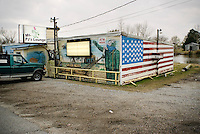 A mural painted on the facade of PJ's Lounge in Montegut, Louisiana depicts the much photographed scene of the toppling of a statue of Saddam Hussein in Firdos Square, Baghdad, next to a mural of the American flag.