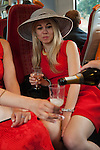 Two young women, drinking champagne from plastic cups on train journey to Royal Ascot.2016, 2010s
