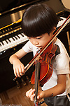 Education Elementary Kindergarten male student playing violin during music lesson at school