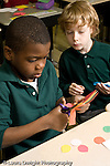 Education Elementary school Grade 2 mathematics two boys working together on project cutting out shapes vertical