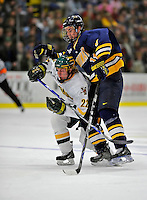 16 February 2008: University of Vermont Catamounts' defenseman Josh Burrows, a Freshman from Prairie Grove, IL, is checked by Merrimack College Warriors' forward Matt Jones, a Sophomore from Kentwood, MI, at Gutterson Fieldhouse in Burlington, Vermont. The Catamounts defeated the Warriors 2-1 for their second win of the 2-game weekend series...Mandatory Photo Credit: Ed Wolfstein Photo