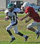 Football action. Running back stiffarms defensive player.