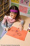 Preschool ages 3-5 girl sitting at table drawing with marker writing letters of name vertical