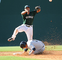 Second baseman Heiker Meneses (21) of the Greenville Drive turns the first half of a double play as J.R. Murphy (21) slides into second in a game against the Charleston RiverDogs on May 15, 2011, at Fluor Field at the West End in Greenville, S.C. Photo by Tom Priddy / Four Seam Images