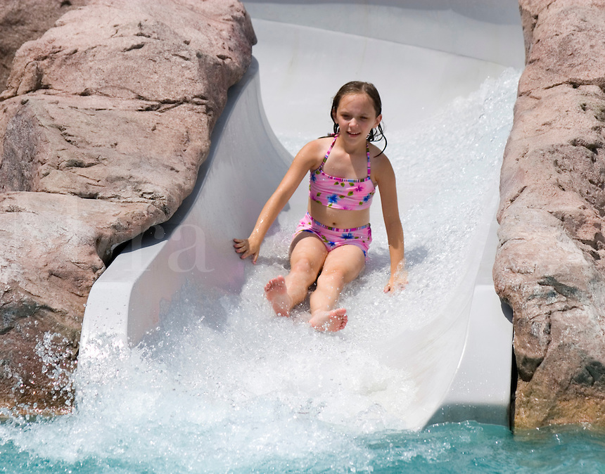 Sliding down a water slide.