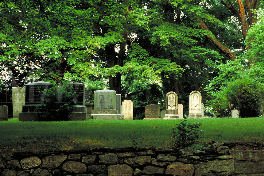 Mead family cemetery with headstones from colonial times forward; large trees; stone retaining wall in foreground. Waccabuc New York.