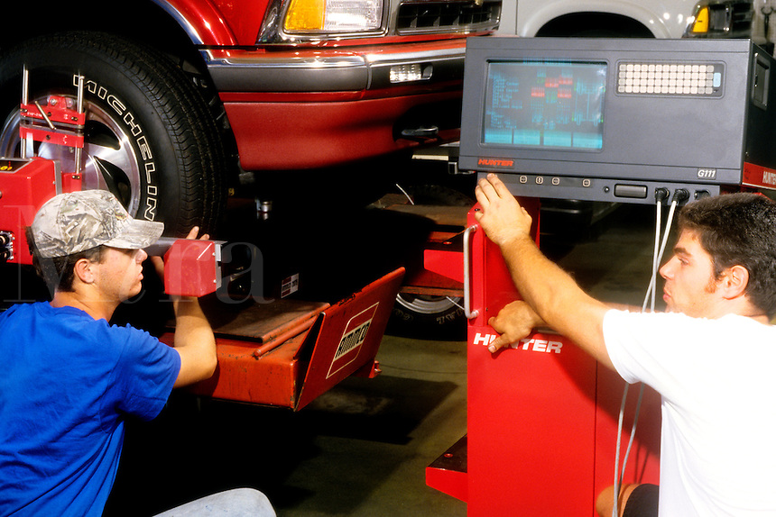College students working at mechanics on auto repair with machiner