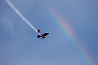 Red vintage biplane flying through rainbow, Arlington Fly-In 2016, Washington State, USA.