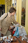 Memory forgetfulness woman in 40s leaving cell phone eelctronic organizer on table of sidewalk cafe walking off with shopping bags