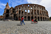 Rome 17/5/2020 <br /> A couple walk and a woman rides a bicycle, all wearing masks, in front of the coliseum during the second phase of lockdown measures decided by italian government due the coronavirus, covid-19, pandemic . <br /> Restaurants, bars and most of the commercial activities will be reopened on 18 May . <br /> Photo Andrea Staccioli / Insidefoto