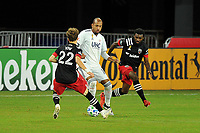 WASHINGTON, DC - SEPTEMBER 27: Teal Bunbury #10 of New England Revolution battles for the ball with Griffin Yow #22 and Chris Odoi-Atsem #3 of D.C. United during a game between New England Revolution and D.C. United at Audi Field on September 27, 2020 in Washington, DC.