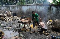NIGERIA, Lagos, Arena Market , selling of live chicken which are immediately butchered here , background cow horns of slaughtered cows / Verkauf von lebenden Huehnern und Schlachtung vor Ort