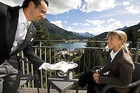 Switzerland. Canton Graubünden. St. Moritz. Butler. Matheus Alcover (L) serves a coffee to a guest on the suite's balcony. Hotel Carlton.  © 2008 Didier Ruef
