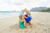 A couple sharing a kiss while playing with their children on Waimanalo Beach, O'ahu.