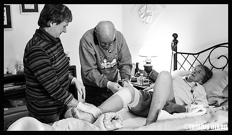 Change of leg dressings by family members;Mom getting her dressings changed by dad and my sister.<br /> <br /> We all did this, twice daily.  <br /> <br /> I photographed each dressings change to monitor wound progress, but this is the one/only time I pulled back to share/show more.