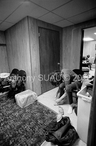 """Denver, Colorado<br /> USA<br /> May 9, 1983.<br /> <br /> Back stage with the Ramones singer: Joey Ramone (tying his shoe), basist: Dee Dee Ramone in back room.<br /> <br /> The Ramones were an American rock band that formed in Forest Hills, Queens, New York in 1974, often cited as the first punk rock group. Despite achieving only limited commercial success, the band was a major influence on the punk rock movement both in the United States and the United Kingdom.<br /> <br /> All of the band members adopted pseudonyms ending with the surname """"Ramone"""", though none of them were actually related. They performed 2,263 concerts, touring virtually nonstop for 22 years. In 1996, after a tour with the Lollapalooza music festival, the band played a farewell show and disbanded.<br /> <br /> By a little more than eight years after the breakup, the band's three founding members--lead singer Joey Ramone, guitarist Johnny Ramone, and bassist Dee Dee Ramone--had all died."""