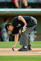 Home plate umpire Brad Myers cleans off home plate between innings of the International League game between the Toledo Mud Hens and the Charlotte Knights at Knights Stadium on May 10, 2012 in Fort Mill, South Carolina.  (Brian Westerholt/Four Seam Images)