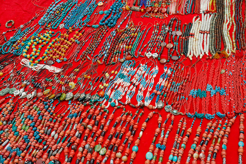 Assortment of Tibetan Buddhist religious jewelry includes rosary, or mala, beads used to count recited mantras, amulets or prayer boxes, and necklaces, made of jade, coral, amber, sandalwood, yak bone, and turquoise, at the entrance to Drepung Monastery, Lhasa, Tibet, China.