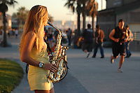 Saturday, January 31 2009:  Pacific Beach, San Diego, California, USA.  Kristen Spees plays her saxaphone on the boardwalk in Pacific Beach just before sunset on a warm Saturday afternoon.  Spees, (22) a law student from Oahu has become a regular fixture on the boardwalk at the bottom of Grand Ave near the main lifeguard tower.