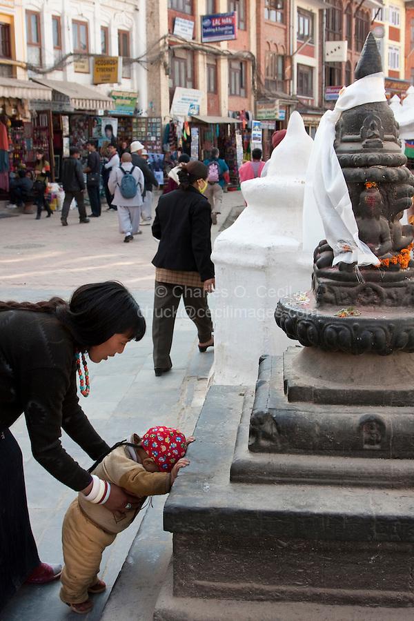 Bodhnath, Nepal.  A Mother Teaches her Child to Pray at a Shrine at the Base of the Bodhnath Stupa, a Tibetan Buddhist Stupa.