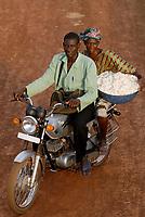 MALI , Bougouni , women harvest fair trade organic cotton, woman with husband and cotton yield on motorcycle / MALI , Bougouni, Fair trade und Biobaumwolle Projekt , Biofarmerin Kéniba Samake mit ihrem Mann Daouda Samaké aus Dorf Faragouaran